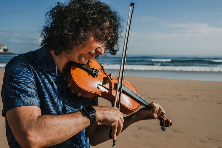 Man playing violin at beach