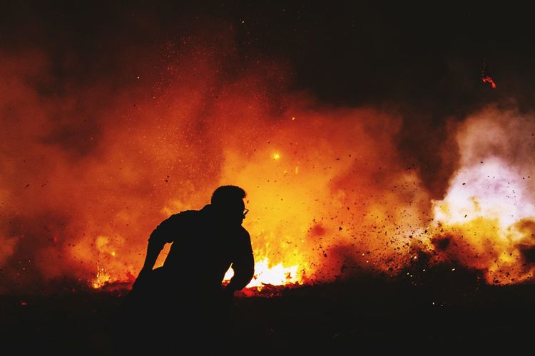 Silhouette man standing against fire at night