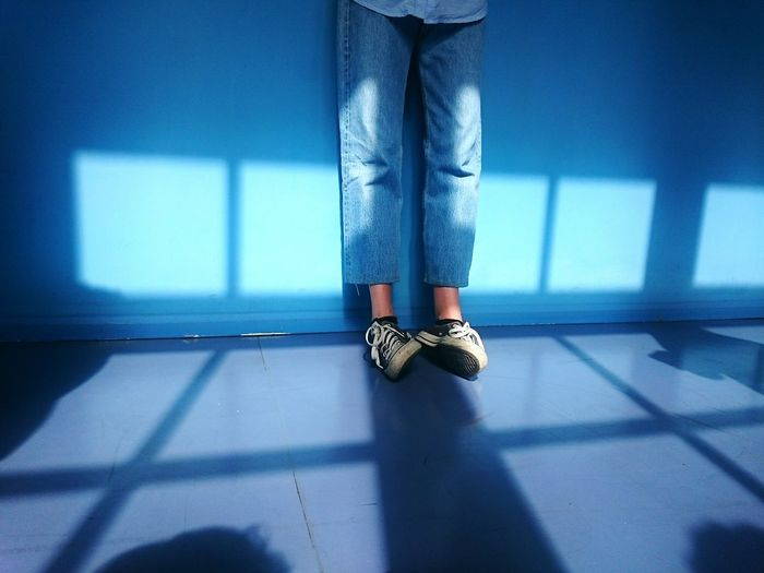 Low Section Of Person Standing Against Blue Wall