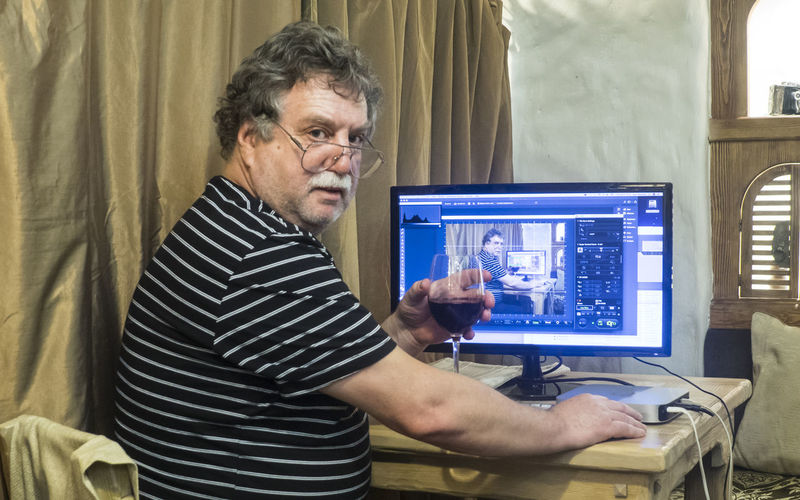 Mature caucasian man with glass of wine sits near computer Man Sit Sitting Adult Adults Only Casual Clothing Caucasian Computer Computer Monitor Day Eyeglasses  Glass Indoors  Love Yourself Mature Occupation One Person People Real People Technology Working