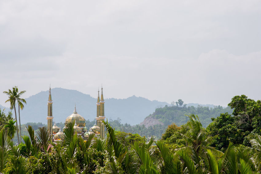 The minarets and dome of the Crystal Mosque or Masjid Kristal in Kuala Terengganu, Malaysia towering above a foreground view of tropical palm trees. Kuala Terengganu Masjid Kristal Architecture Beauty In Nature Building Exterior Built Structure Crystal Crystal Mosque Dome Malaysia Minaret Mosque Mosque Architecture Nature Outdoors Place Of Worship Religion Sky Spirituality Tree