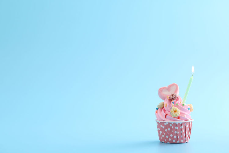 Low angle view of cupcakes against blue background