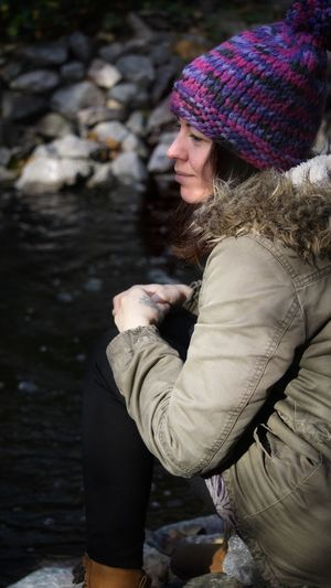 Side View Of Woman Wearing Warm Clothing Sitting By Lake