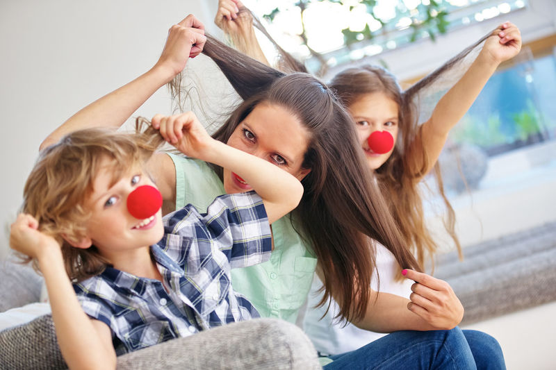 Portrait Of Funny Family Wearing Clowns Nose While Holding Hair On Sofa At Home