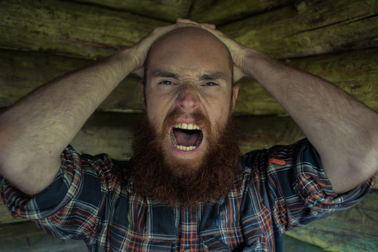 Close-up portrait of frustrated bald man screaming in log cabin