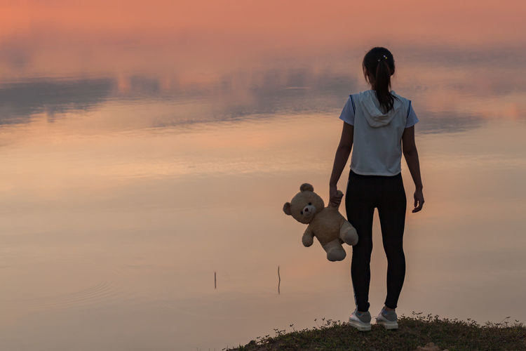 Rear View Of Woman Holding Teddy Bear While Standing Against Lake During Sunset