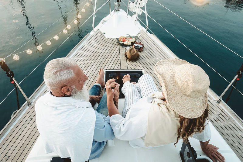 High angle view of couple holding hands while sitting in boat
