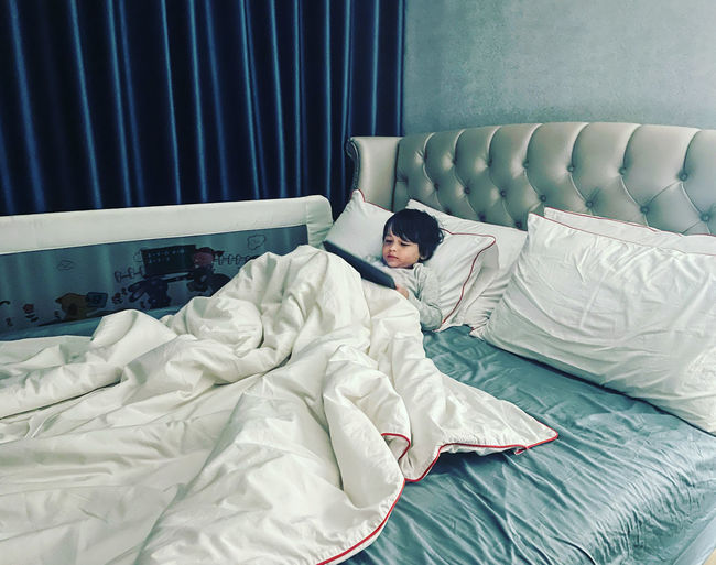 Midsection of boy resting on bed at home