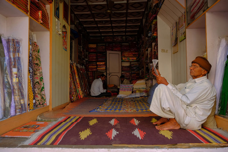 Daily life of streen market in Mandawa, India. Mandawa, Rajasthan Architecture Bed Belief Carpet - Decor Floral Pattern Full Length Furniture Home Interior Indoors  Lifestyles Males  Mandawa Men People Place Of Worship Real People Relaxation Religion Sitting Spirituality