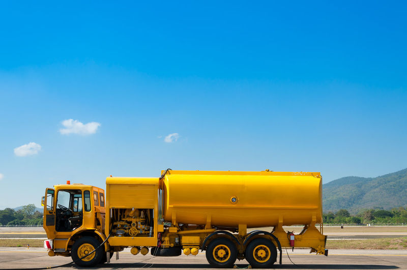 yellow truck with fuel tank on runway Gasoline Tankers Fuel Gas Lorry Service Tanker Transport Transportation Airfield Airport Blue Car Construction Site Highway Industry Land Vehicle Oil Refuel Tank Transportation Truck Vehicle Water Yellow