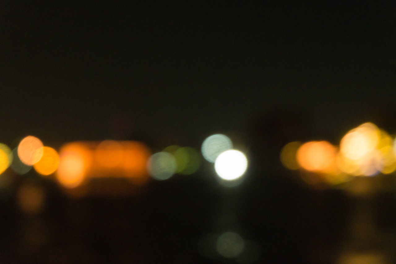 DEFOCUSED LIGHTS AGAINST SKY AT NIGHT