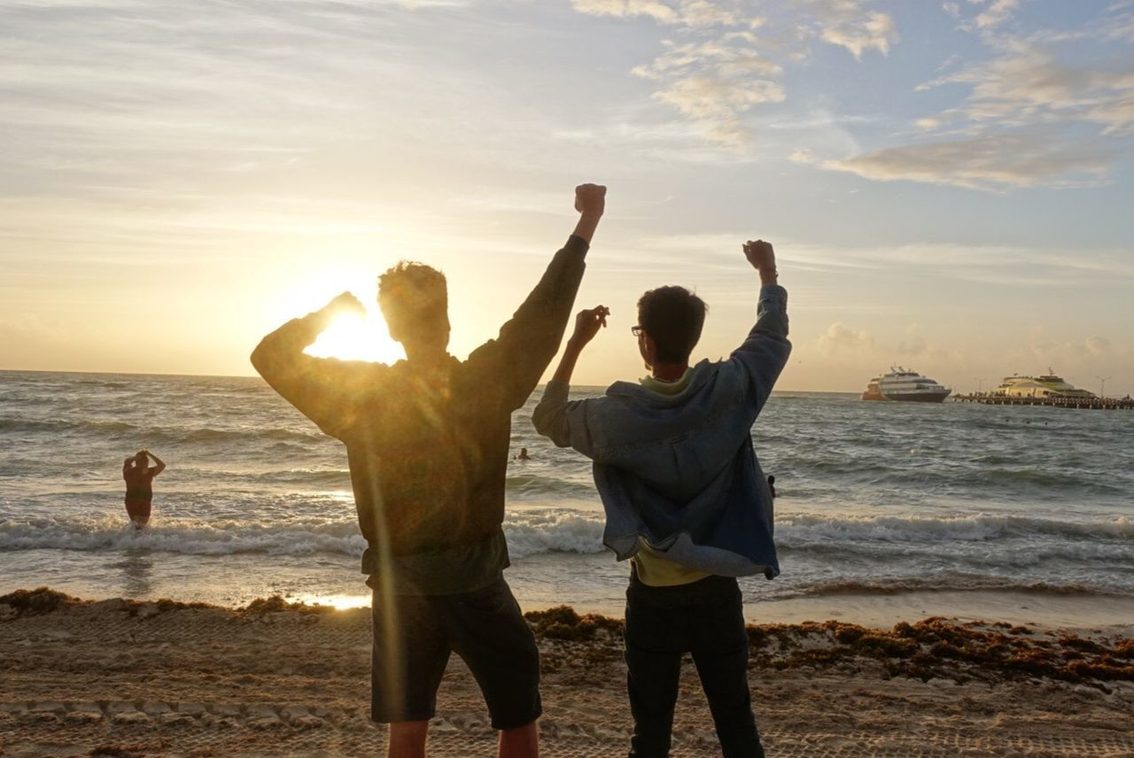 sea, water, sky, land, beach, real people, arms raised, human arm, togetherness, leisure activity, two people, men, lifestyles, sunset, standing, beauty in nature, positive emotion, scenics - nature, rear view, horizon over water, outdoors, couple - relationship
