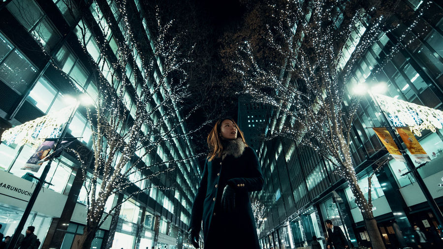 Low angle view of woman looking at illuminated tree