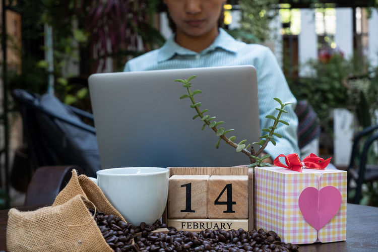 Midsection of woman using laptop at table with date