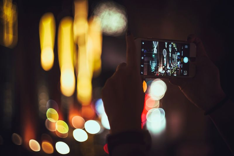 Cropped Image Of Man Photographing Illuminated City At Night