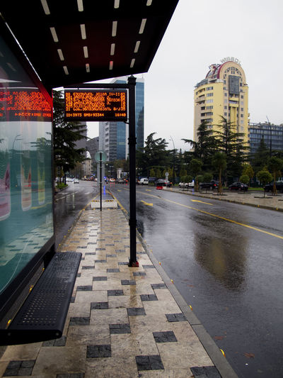 Wet street amidst buildings in city during rainy season