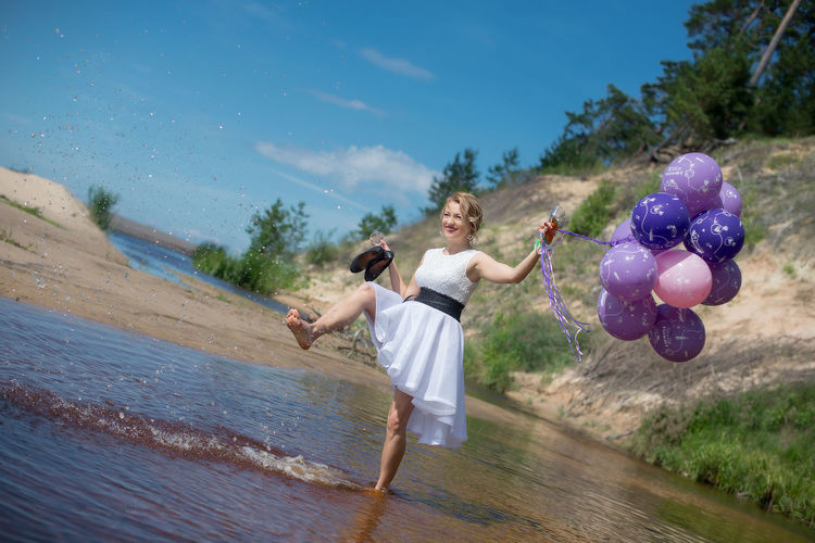 Woman kicking water and holding balloon
