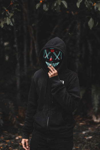 Man wearing mask in forest