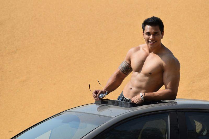 Shirtless smiling muscular man standing in sun roof at desert