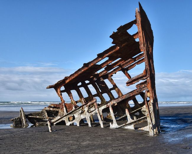 Old wooden structure on beach against sky