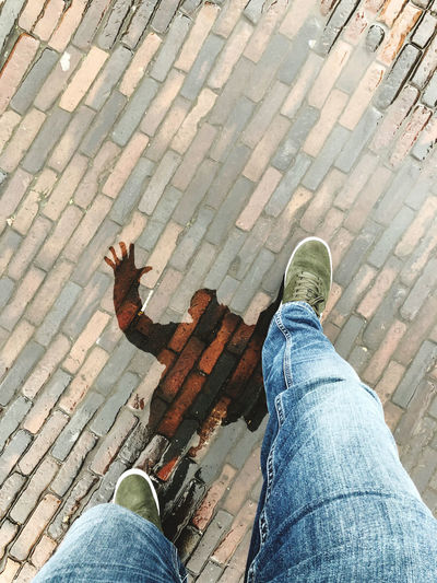 Low section of man walking on wet cobblestone street with reflection