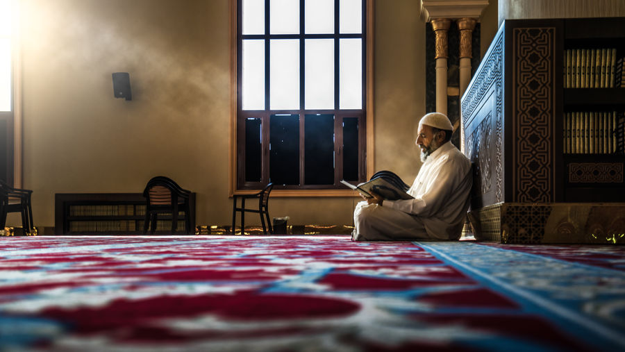 Surface Level Of Man Reading Quran In Mosque