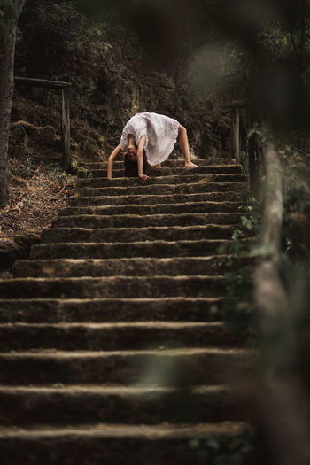 Low angle view of woman on staircase in forest