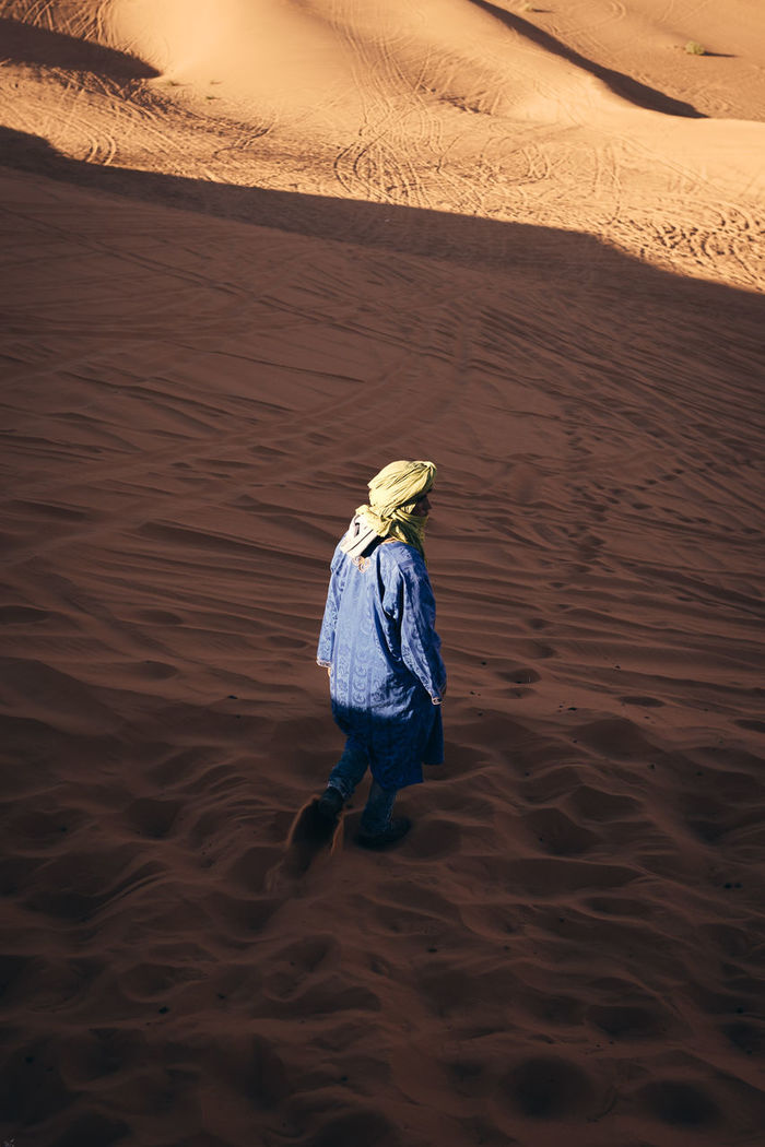 REAR VIEW OF PERSON WALKING ON SAND AT BEACH