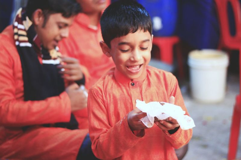 Happy boy holding cake in tissue paper