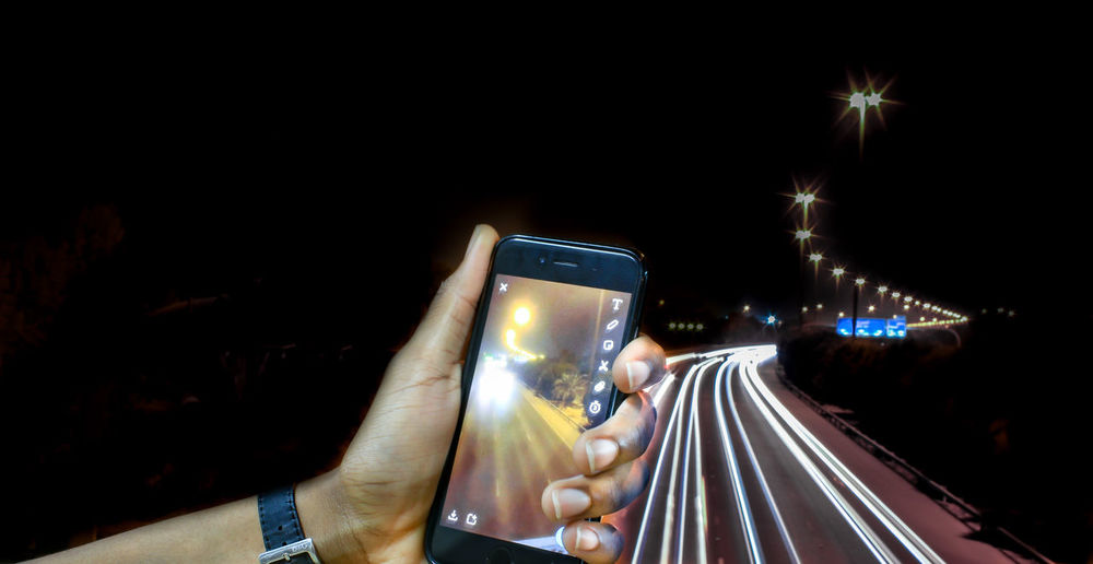 Close-up of hand photographing illuminated smart phone at night