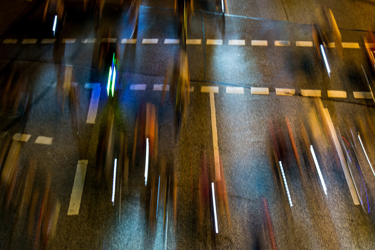 Blurred motion of people riding bicycles on street at night