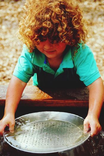 High Angle View Of Cute Boy Holding Colander On Water