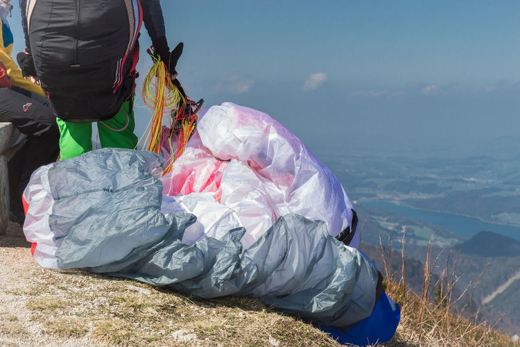 People on mountain preparing for paragliding