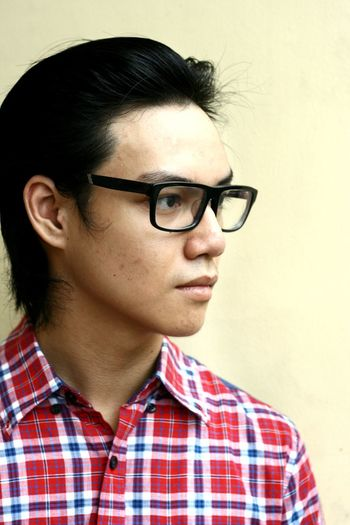 Thoughtful Young Man Wearing Eyeglasses Against Wall