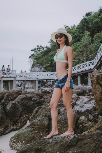 Full length of woman standing on rock at beach