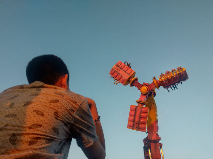 Low angle view of man with toy against sky