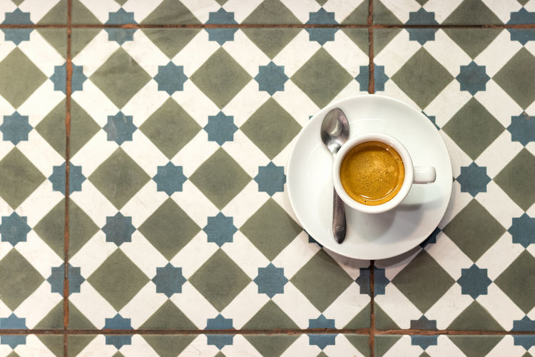 A cup of coffee espresso on a plate with spoon placed on an old ceramic tile floor. Above Background Breakfast Brown Ceramic Coffecup Coffee Cup Design Element Espresso Floor Hot Minimal Mug Office Old One Pattern Plate Retro Rustic Single Spoon Texture Tile Top View Vintage White