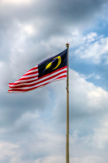 State flag of Malaysia And Johor bahru Flag.Malaysia flag also known as Jalur Gemilang wave with the blue sky. People fly the flag in conjunction with the Independence Day celebration or Merdeka Day.Johor Bahru is One of the states under the administration of malaysia Cloud - Sky Day Emotion Environment Flag Independence Low Angle View Nature No People Outdoors Patriotism Pole Red Sky Striped Waving Wind