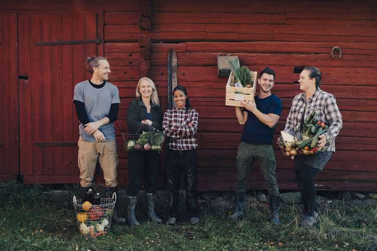 Full length of multi-ethnic farmers with organic vegetables standing against barn