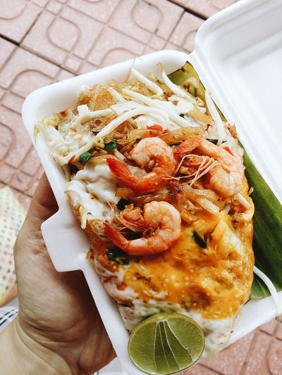 Cropped Hand Holding Pad Thai In Disposable Container