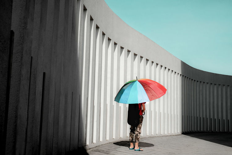 Rear view of a boy with umbrella standing on driveway