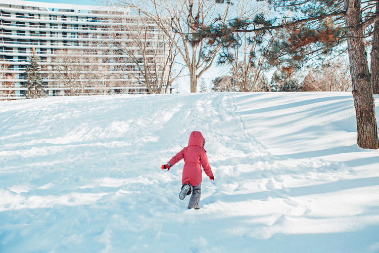 Girl child in warm clothes running in snow park outside. child kid having fun on winter day