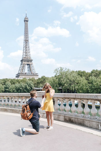 Man proposing woman on road against eiffel tower in city