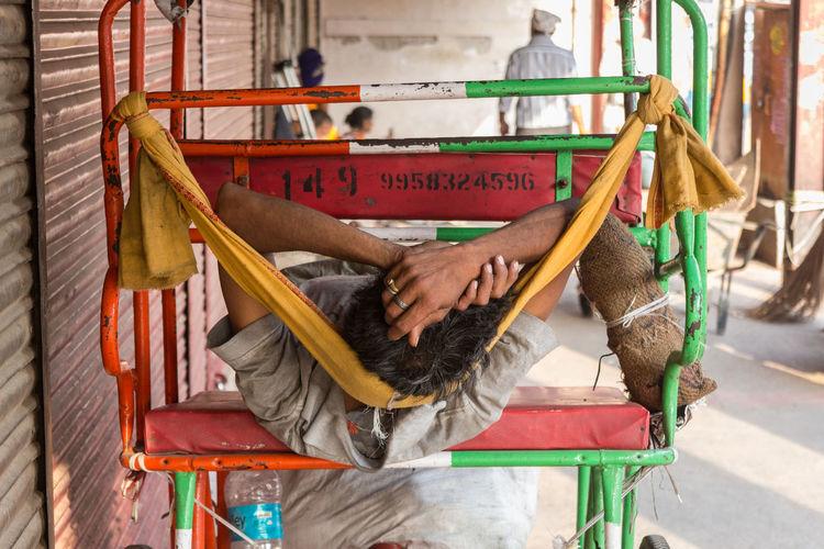 Man sleeping on jinrikisha on footpath