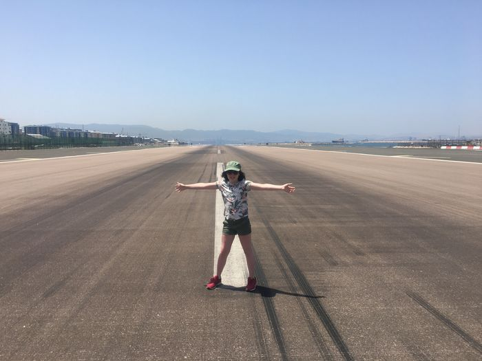 Full length of girl with arms outstretched standing on airport runway