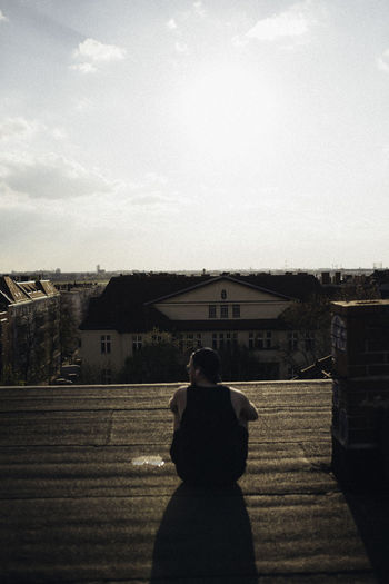 Rear view of woman standing by buildings against sky