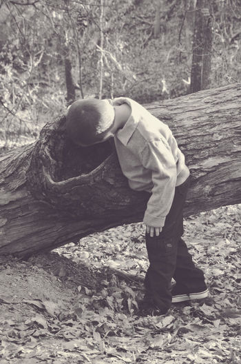 Explore Boy Casual Clothing Day Explore Leisure Activity Log Looking In Nature Outdoors Tree Tree Trunk Black And White