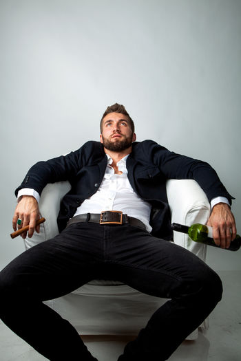 Portrait of a bearded businessman with a cigar and a bottle of wine in his hand, is sitting in a white armchair and relaxing Sitting Men Front View Males  One Person Indoors  Portrait Adult Beard Businessman Suit Handsome Bottle Wine Cigar Holding Looking At Camera Relaxing Armchair White Fashion Lifestyles Alkohol Bad Habit Manager