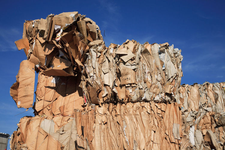 Low Angle View Of Stacked Papers At Junkyard Against Sky