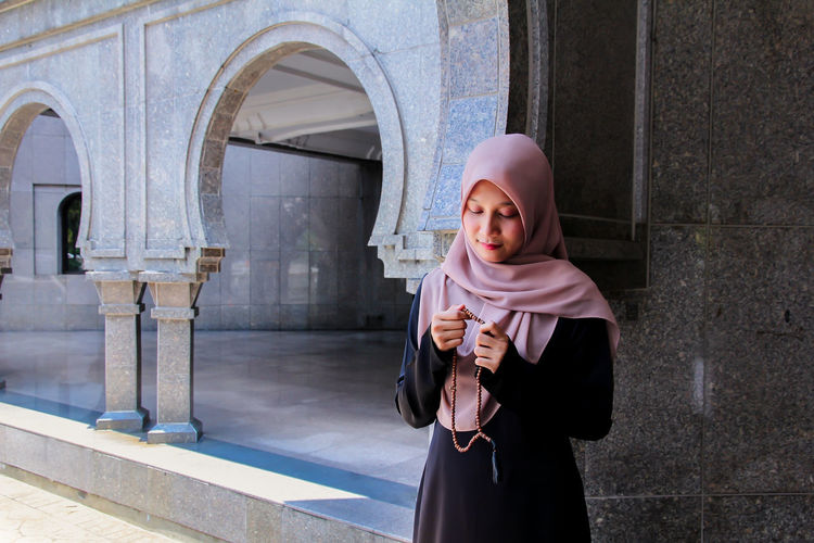 Woman in hijab holding counting rosary beads while praying at mosque
